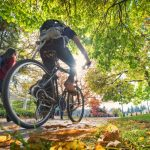 person biking through campus in autumn